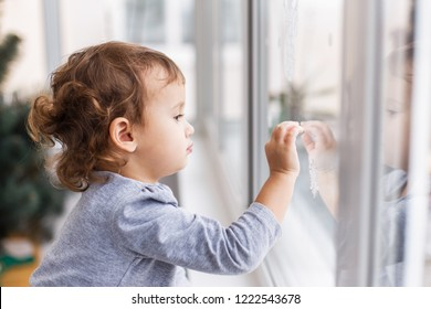 Cute little three years girl looking through window with holiday decoration. Christmas and New Year window decoration