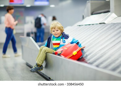 Cute little tired kid boy at the airport, traveling. Upset child waiting with kids suitcase on baggage carousel. Canceled flight due to pilot strike.