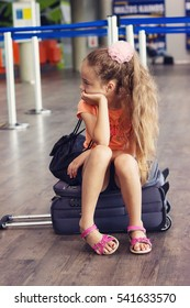 Cute little tired Kid Girl at the Airport, traveling. Sad Child waiting and sitting on Suitcase. Canceled flight due to pilot strike.