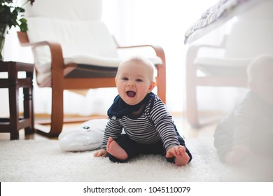 Cute little toddler baby boy, playing at home on the floor in bedroom, baby reflection on the bed, smiling happily