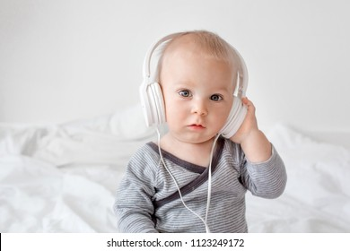 Cute little toddler baby boy listening music with head phones in bed