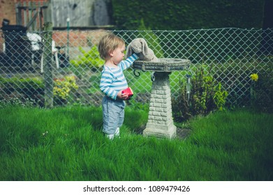 A cute little toddler boy is standing by a bird bath with his soft toy