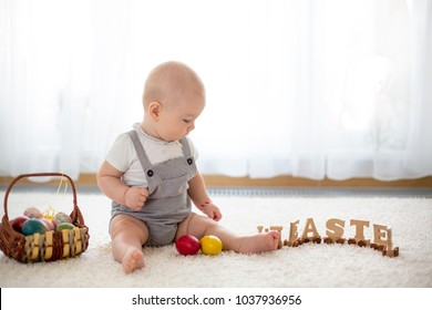 Cute little toddler child, baby boy, in sunny living room playing with  Easter chocolate bunny and colorful Easter eggs