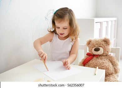 Cute little toddler child drawing with pencils. Adorable baby girl drawing on white paper near window in light room