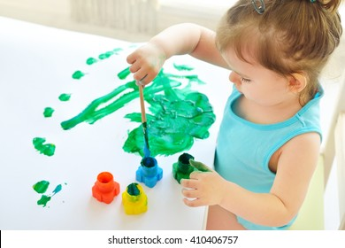 Cute little toddler child painting with paintbrush and colorful paints. Adorable baby girl drawing on white paper near window in light room