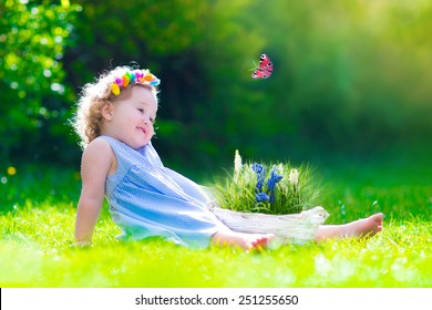 Cute little toddler girl with curly hair wearing a blue summer dress having  fun watching a 0256ff0c85e6
