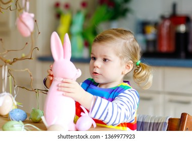 4d31ced1c865 Cute little toddler girl decorating tree and bunny with colored pastel  plastic eggs. Happy baby