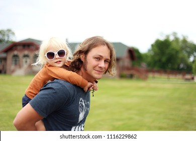 A cute little toddler girl with fashionable sunglasses is getting a piggy back ride from her handsome, long haired father.