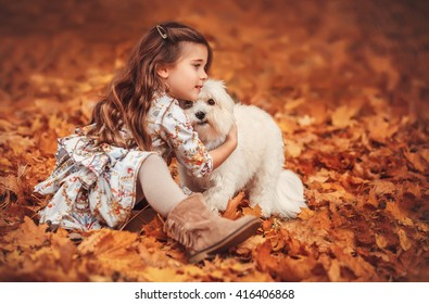 A cute little toddler girl giving a hug to her dog, a yellow in a park with autumn trees in the background