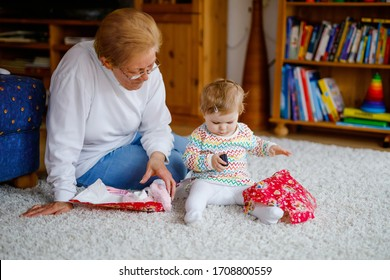 Cute little toddler girl and grandmother playing with toys at home. Adorable baby child and senior retired woman unpacking gifts for birthday. Happy family together