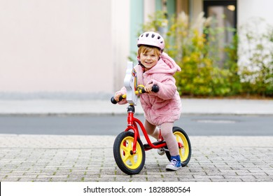 Cute little toddler girl with helmet riding on run balance bike to daycare, playschool or kindergarden. Happy child having fun with learning on learner bicycle. Active kid on cold autumn day outdoors.