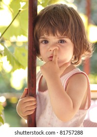 Cute little toddler girl picking her nose