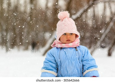 cute little toddler girl play in winter snow