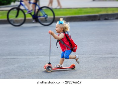 cute little toddler girl riding scooter in the city, kids sport