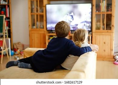 Pequeña niña y niño de escuela cutáneo viendo películas de animales o películas en televisión. Felices niños sanos, hermanos durante la cuarentena del coronavirus que se quedan en casa. Hermano y hermana juntos. sin cara