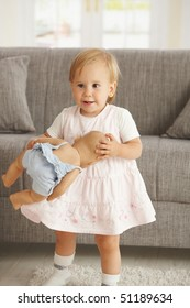 Cute little toddler girl standing in living room holding dolly, smiling.