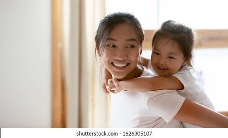 Cute little Vietnamese girl piggyback overjoyed ethnic young mother having fun at home, small smiling Asian daughter child play with happy biracial millennial mom or nanny, entertainment concept