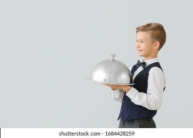 Cute little waiter on light background