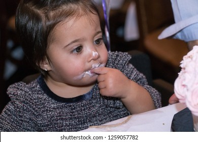 Cute little young baby girl celebrate birthday party taste delicious tasty cake decorative frosting with fingers and gets all over face mouth and nose. Funny lifestyle authentic family moment