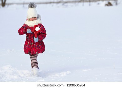 Cute little young funny toothless child girl in warm clothing playing having fun making snowballs on winter cold day on white bright blurred copy space background. Outdoors activity, holiday games.