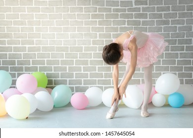 Cute little young girl ballerina dancer in pink leotard and tutu are dancing in studio room with pastel colors balloon. Pretty child girl kid in ballet costume do ballet dance practice in the room.