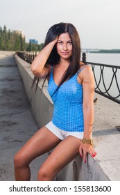 cute long haired 20s Russian brunette weared blue tank top and shorts outdoor on riverside. Toned cross process color image. Touch hair by hand