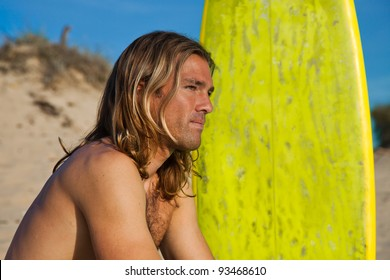 Cute long haired blonde surfer sitting next to his surfboard.