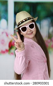 Cute long haired girl in hat and sunglasses shows victory sign - children beauty and fashion concept