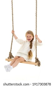 Cute long haired girl sitting on rope swing