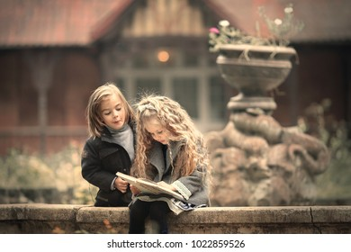 Cute long-haired blonde girl is reading a book sitting on the edge of old dried fountain in autumn. Funny boy is looking over her shoulder with funny expression. Image with selective focus and toning.