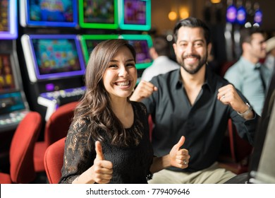 Cute looking couple going to the casino for a date and having some fun playing slots