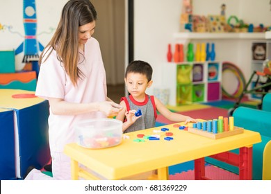 Cute looking kid and a female language therapist looking at some letters and practicing the alphabet