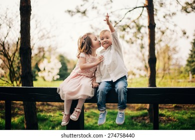 Cute love. Little girl kissing little boy outdoors in park