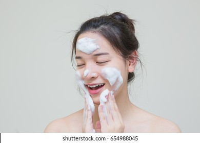 cute lovely Asian young girl with calm and relax emotional face enjoy her skin care product that she use