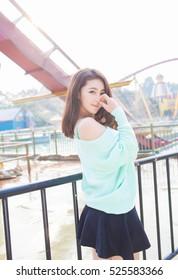 süße schöne japanische Mädchenfrau mit großen Brüsten und Aquamarine Pullover, kleiner Mini-Rock im Freien haben Freude beim Spielen im Freizeitpark Karneval während der Reise