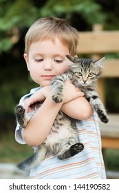 Cute lovely boy with kitten in a park