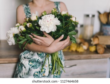 Cute and lovely peony flowers in women's hands.. many layered petals. Bunch pale white peonies flowers light gray background. Wallpaper,lifestyle