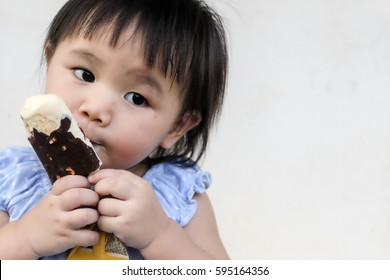Cute Lovely thai little kid eating ice cream with mouth smeared vanilla ice cream