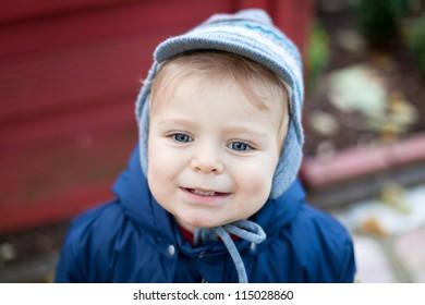 Cute lovely toddler in autumn garden in warm clothes