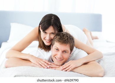 Cute lovers looking at the camera on their bed