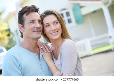 Cute loving couple standing in front of home and laughing