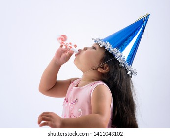 cute malay girl wearing party hat blowing noise maker on the gray background