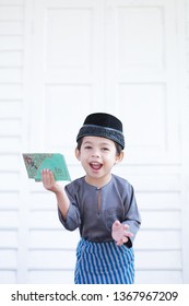 Cute Malay Muslim boy with exciting facial expression when receiving a Duit Raya with nice grey coloured Baju Melayu outfit over beautiful traditional wooden Malay house during Eid Fitri in Malaysia
