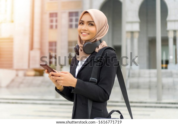 Cute Malay Woman wearing headset outdoor listening to the music and playing with the phone