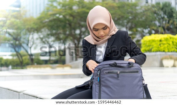 Cute Malay Woman wearing hijab outdoor sitting and looking inside bag
