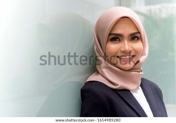 Cute Malay Woman wearing hijab outdoor executive smile to the camera