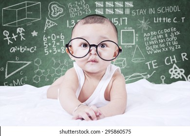 Cute male baby looking on the camera while wearing glasses, shot with a doodles background on the blackboard