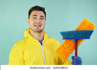 Cute male cleaner in a yellow suit with a mop and a broom in his hands on a turquoise background, stand and smile. Cleaning concept. Male cleaner.