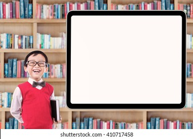 Cute male elementary school student standing in the library while laughing near the whiteboard