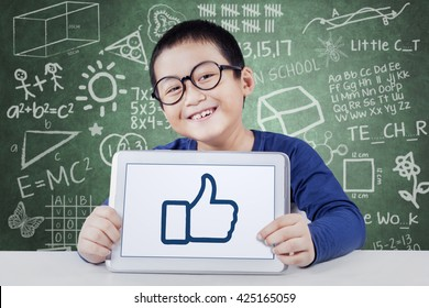 Cute male elementary school student smiling at the camera while showing thumb up on the tablet screen, shot in the classroom